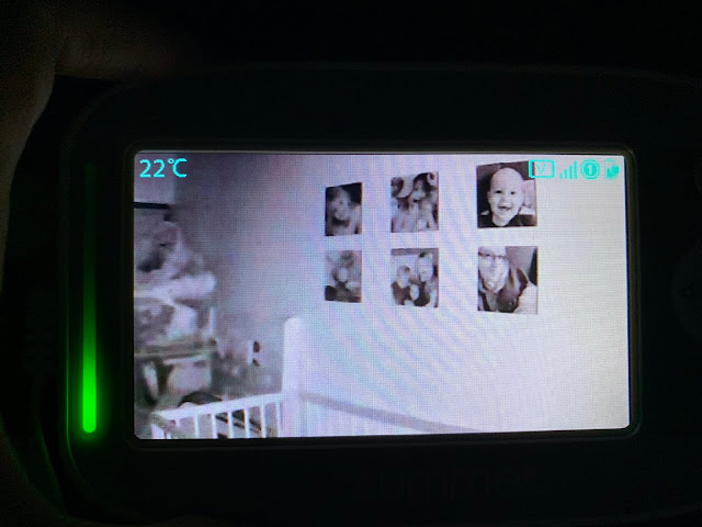 View of handheld monitor at night with camera directed towards photographs on the wall behind the cot