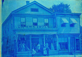 19th century store in blue tint with staff on steps in front. Photo probably taken 1910 or earlier.