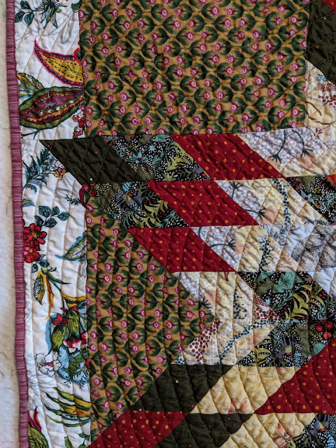 A closeup of the quilt highlights the spiral quilting and the pink stripe binding.