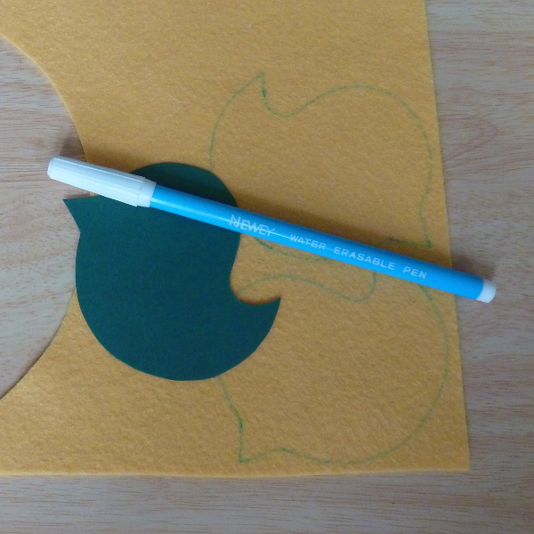 Yellow felt fabric with cardboard bird template fabric marker pen tracing design