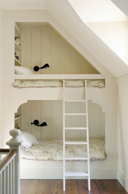 Bunks under a sloping roof, like in this loft space, are a great solution where precious floor space is eaten by a central stairwell