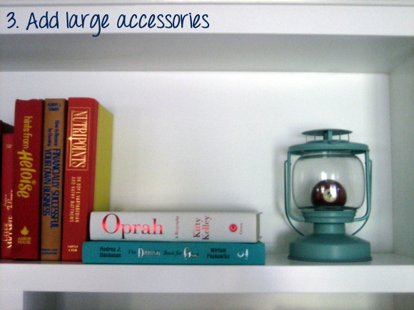 Add a large accessory like this vintage lamp to the books.