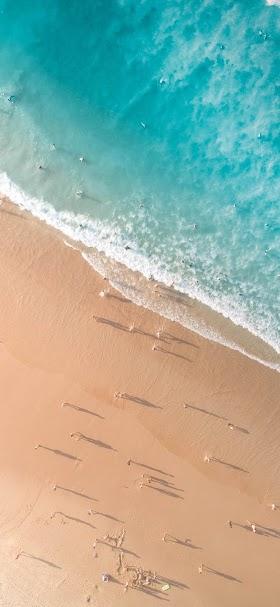خلفية صورة جوية لالتقاء الأمواج الصافية برمال الشاطئ النقية