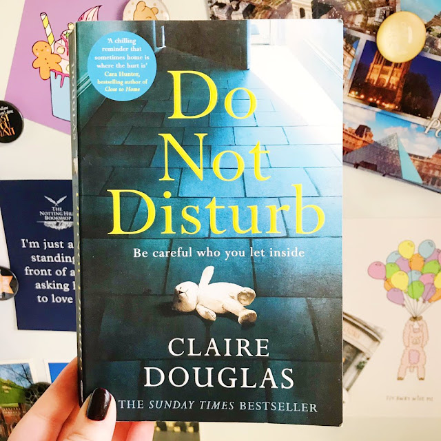 Do Not Disturb by Claire Douglas book held up in front of desk