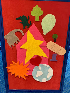 flannel board with flannel pieces in the shapes of a large house, star, burst, heart, earth, elephant, small beast, plant, balloon, small tree, bandage, and magic hat
