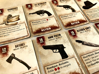 A selection of equipment cards from The Walking Dead: All Out War miniatures game