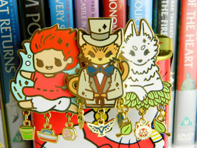 A photo of three enamel pins made by PokoPins, of Studio Ghibli characters, Ponyo, The Baron and Moro