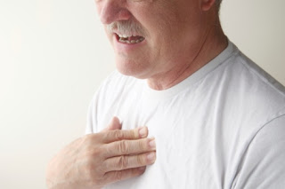 A man touching his sternum in pain