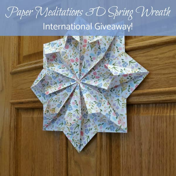 origami floral paper wreath hanging on wooden door