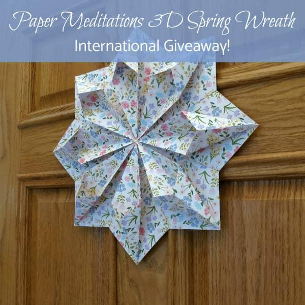 origami floral paper wreath hanging on wooden door