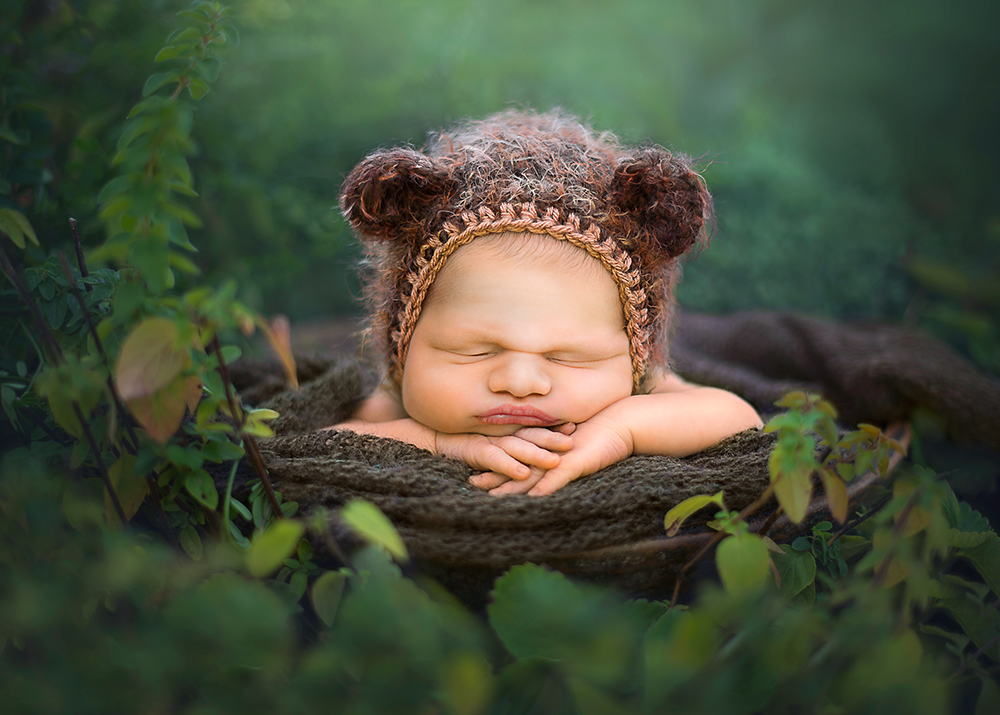 outdoor newborn in a bear hat greenery in the background DeKalb best newborn photographer in Sycamore IL