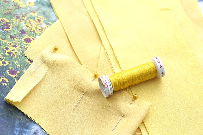Gebügelte gelbe Stoffstücke mit gelber Nähgarnrolle