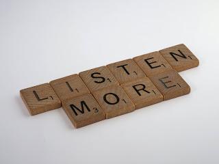"letter tiles arranged to say ""listen more"""