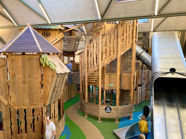 Wooden tree house like structures and metal slides at the Hootz House soft play indoor play area at Pensthorpe North Norfolk