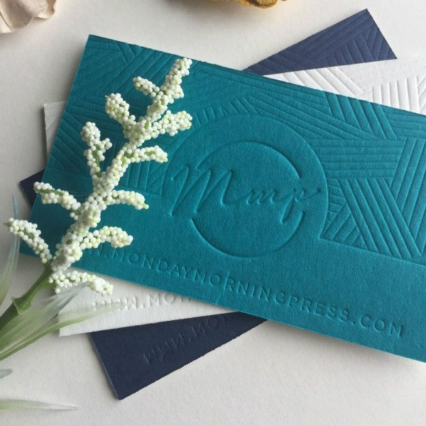 stack of three letterpress business cards in dark blue, white, and teal