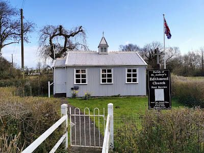 Photograph of a small, corrugated iron building painted light grey with white windows and trim. It is rectangular, with three rectangular windows and a small porch to the left with a door facing the viewer. The roof, bowed downwards in the middle, has a little steeple with a cross on top. The building has a lawn and path in front of it, with a white gate and hedge in the foreground; next to the gate is a sign saying 'Parish of St Andrew's, Edithmead Church' with a notice for service times. Behind, trees and fields are visible.