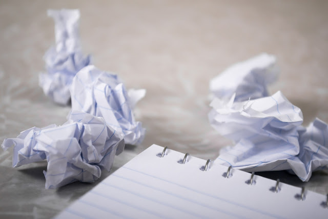 discarded, crumpled paper balls sitting on a counter next to a notepad