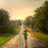 Picture of a woman walking alone down a path in the rain, carrying a rainbow coloured umbrella