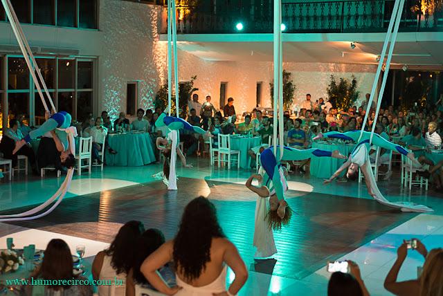 4 acrobatas em tecido se apresentando no meio do salão rodeadas por mesas com convidados do evento de lançamento de produto da empresa Servier do Brasil no Costa Brava Clube no Rio.