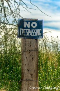 """Cramer Imaging's photograph of an old """"no trespassing"""" sign on a fence post with grass in Pocatello, Bannock, Idaho"""