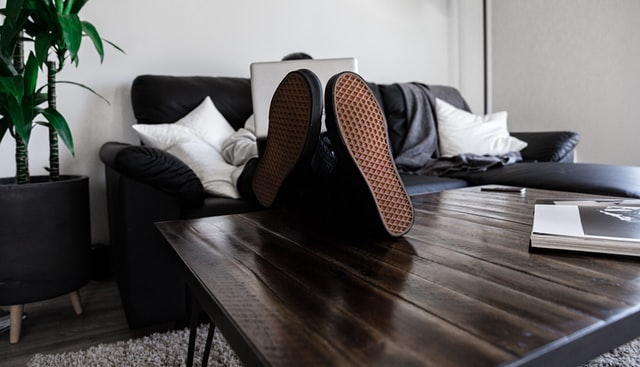 pessoa sentada no sofá com os pés sobre a mesinha da sala