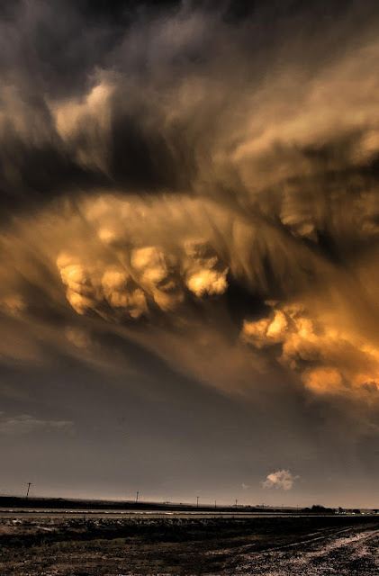 Mammatus clouds break out of the back side of a severe thunderstorm