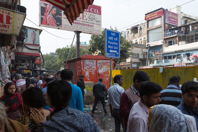 paratha wali gali signpost in Chandni Chowk area Old Delhi market with people in India