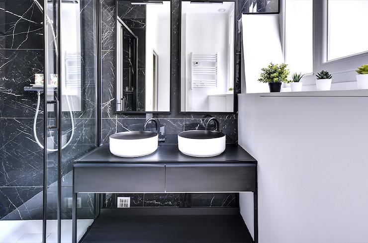 Baño clásico renovado de mármol blanco y negro con ducha y mobiliario a medida.