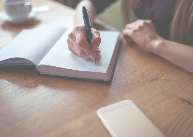 Lady sat at desk writing in journal in a post about the fantastic benefits of journaling for your wellbeing.
