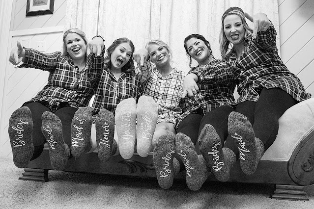 B&W Bride and Bridesmaids in flannel showing off personalized first and last name socks Magnolia Farm Asheville Wedding Photography captured by Houghton Photography