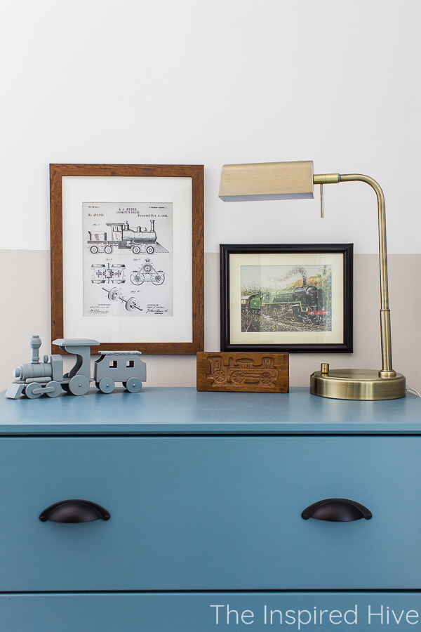 Blue dresser, brass lamp, and vintage train art