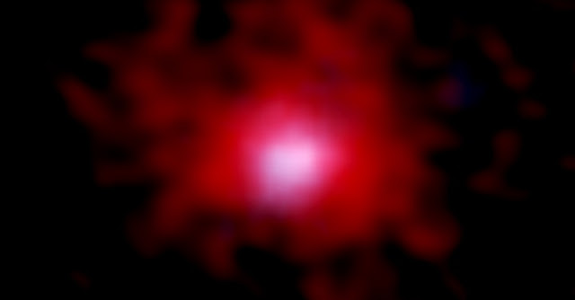 ALMA and NASA/ESA Hubble Space Telescope (HST) image of a young galaxy surrounded by a gaseous carbon cocoon. The red color shows the distribution of carbon gas imaged by combining the ALMA data for 18 galaxies. The stellar distribution photographed by HST is shown in blue. The image size is 3.8 arcsec x 3.8 arcsec, which corresponds 70,000 light years x 70,000 light years at the distance of 12.8 billion light years away. Credit: ALMA (ESO/NAOJ/NRAO), NASA/ESA Hubble Space Telescope, Fujimoto et al.