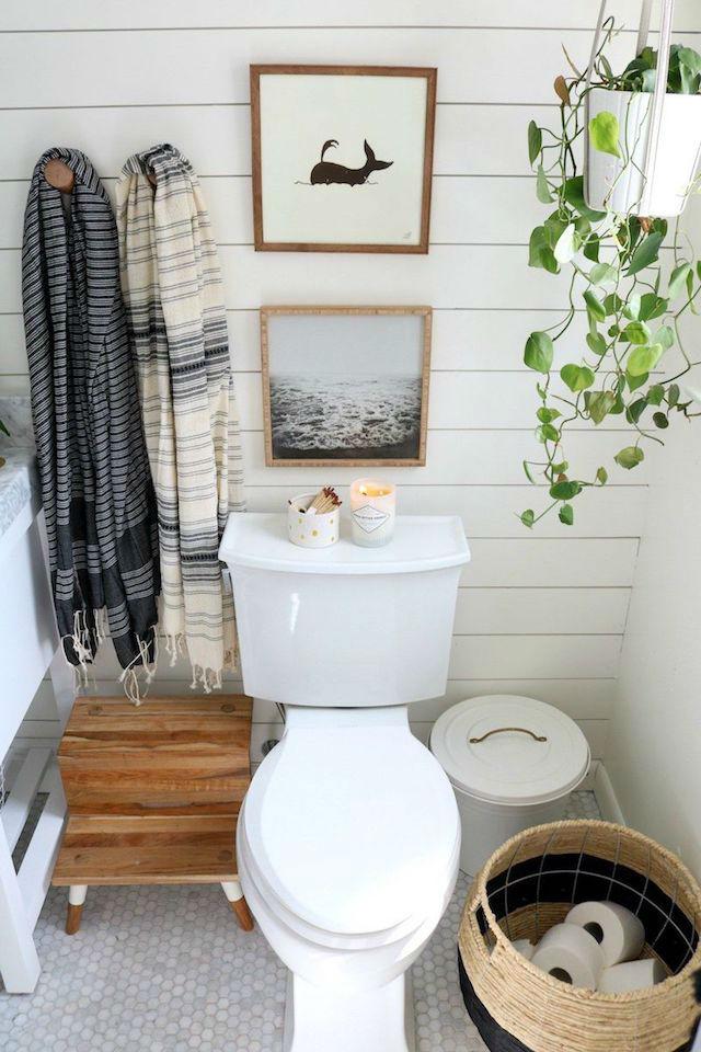 10 ideas para renovar el baño por menos de 100€. Baño antiguo con friso de madera, colgadores de madera, velas, plantas y cuadros.