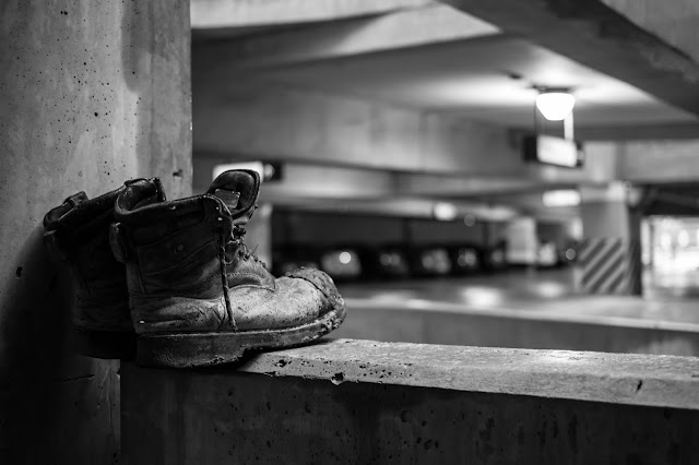 A dirty old pair of boots in a parking garage.