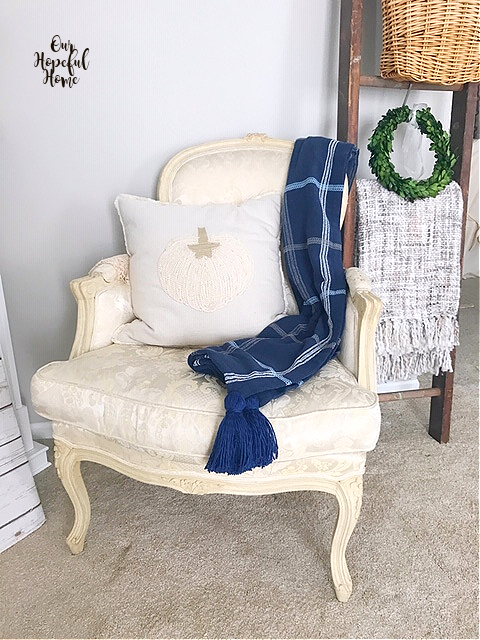 French bergere chair with pumpkin pillow and navy blue throw