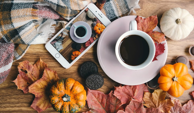 Autumn flatlay with blanket, phone, coffee, leaves and pumpkins