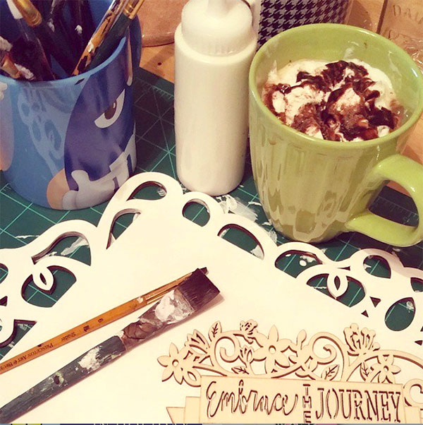 embrace the journey wood carving, frame, brushes, cup of copy and blue mug