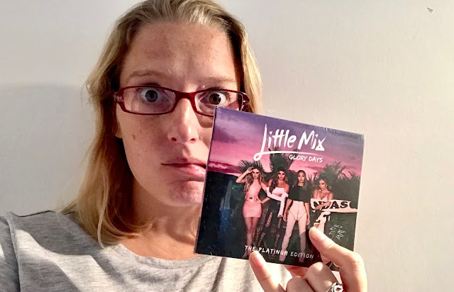 Me pulling a worried face hiding behind a Little Mix glory days CD