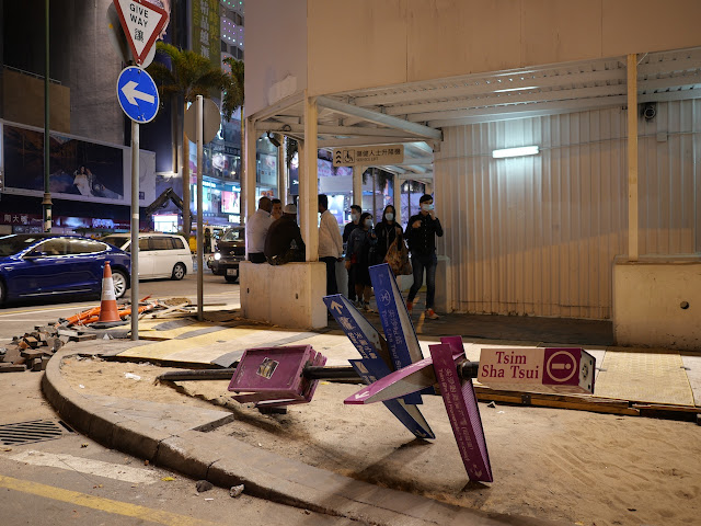 pole with directional signs for pedestrians that was bent down to the ground by protestors in Hong Kong