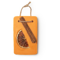 A large rectangular light brown bath oil with a piece of light brown rope on the top with a dark brown cinnamon stick and a dehydrated semi circular light brown piece of orange embedded into the tablet on a bright backgtound