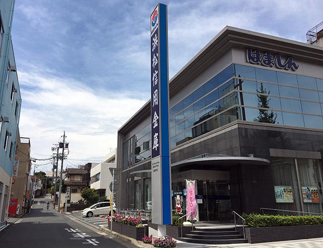 浜松城大手前の諏訪神社大祝家邸宅跡地に建つ浜松信用金庫伝馬町支店と諏訪神社参道、遠く坂上にははまホールが見える(2017年8月23日撮影)