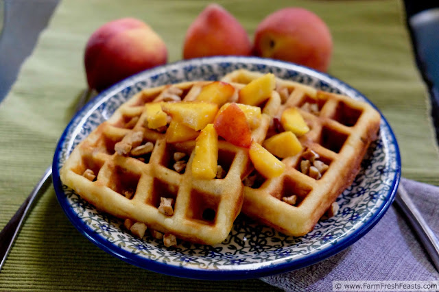 plate of peach and pecan waffles topped with fresh peaches and chopped pecans