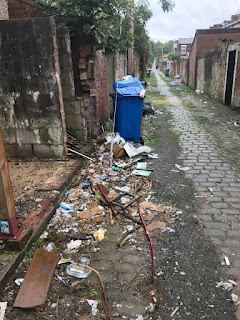 domestic rubbish and overflowing bins in an alleyway