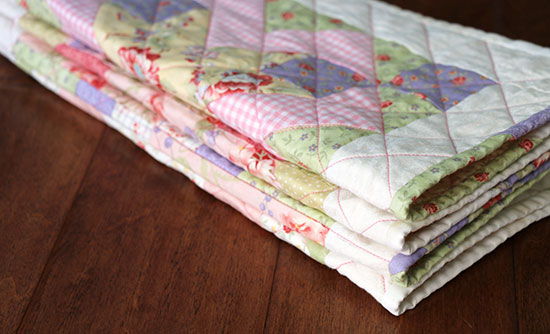 A neatly folded quilted table runner made from pastel floral cotton fabrics, resting dark wood.