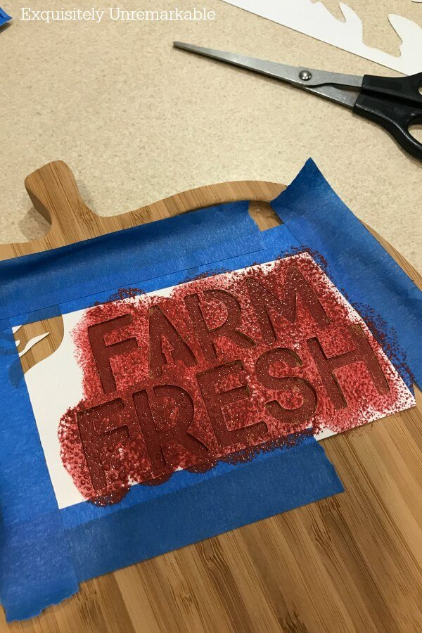 Farm Fresh Stencil taped to cutting board and covered with red paint