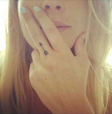 Vemos un tatuaje de flecha solitaria en el dedo de una mujer