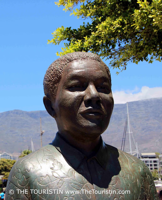 The upper half of a larger than life bronze statue of Nelson Mandela under a bright blue sky in front of a mountain.