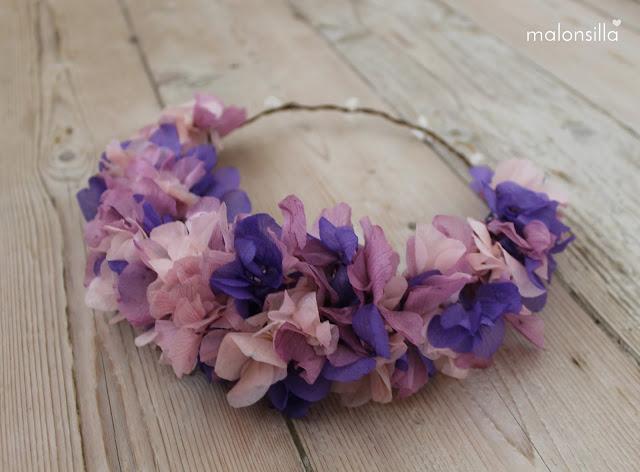 Diadema de flores naturales color morado sobre fondo de madera