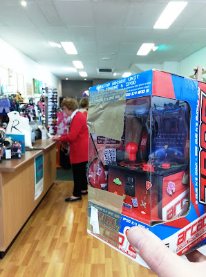 Toy arcade game in its packaging, being held up in an op shop.