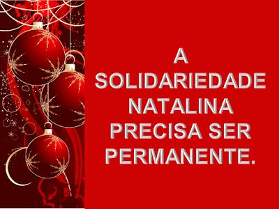 A imagem ao lado esquerdo tem enfeites de Natal e com fundo vermelho e com caracteres em branco diz: A solidariedade natalina precisa ser permanente.